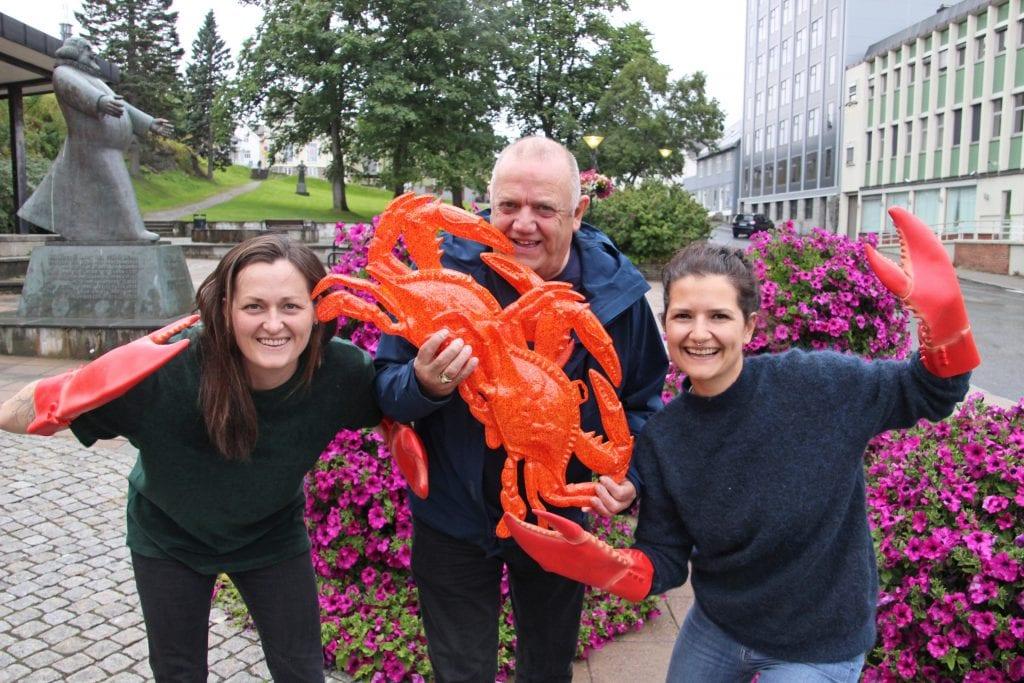 Knut Nilsen klar til å sette tennene i ei krabbe. Han, Senta-Rebecca Lürssen (t.h.) og Stine Aleksandersen gleder seg til sjømatfestival i Sandnessjøen.